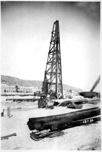 מנוף בעבודה במהלך הבנייה של נמל חיפה. ברקע מתנשא הכרמל באדיבות גיורא בן דב ורוני קנינסברג
