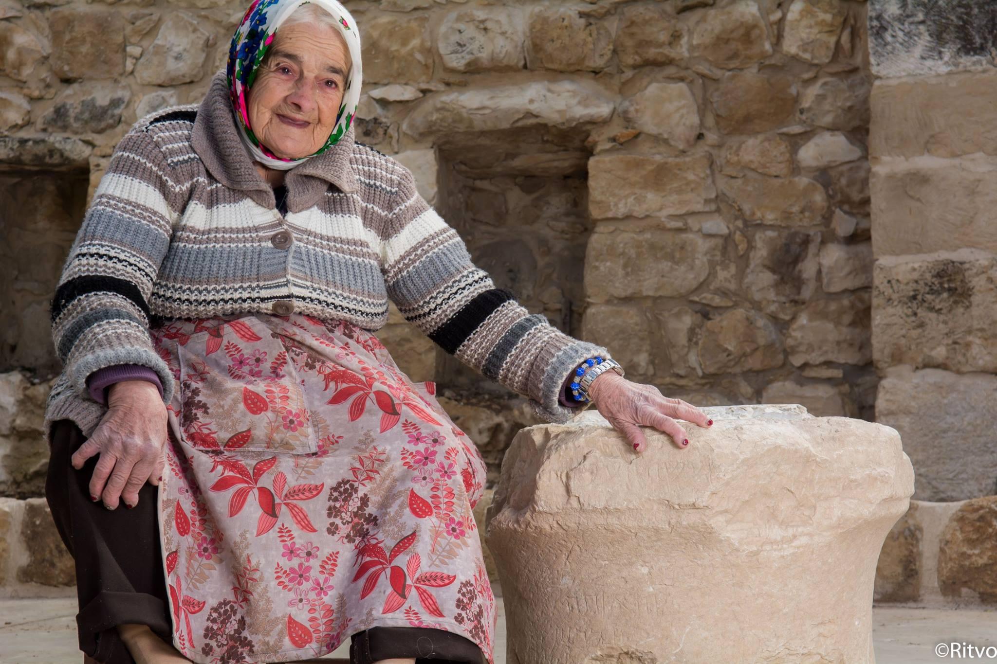 מרגלית זינאתי ליד האבן עם הכתובות שהתגלתה לאחרונה. צילום: Ritvo, באדיבות בית זינאתי
