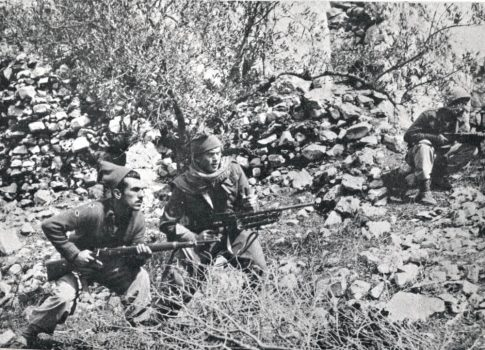 Palmach fighters crouch between stone terraces by San Simon Monastery, waiting for the commander to advance