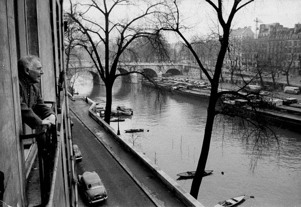 Chagall looking out over the river Seine from the window of his home in Paris