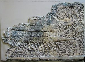 """בקרבות ימיים שהתרחשו בעת העתיקה ניסתה כל ספינה להתנגש בירכתיים של יריבתה כדי לבקוע בה חור או להפוך אותה. תמונת תבליט מארמון סנחריב שבנינווה (705־681 לפסה""""נ) מציגה ספינה פניקית דו טורית הממוגנת בעזרת מגנים המהודקים לשלדתה. הקשת המחודדת שבקצה הספינה היא איל ניגוח ששימש לניגוח ספינות האויב. התבליט מוצג במוזאון הבריטי"""