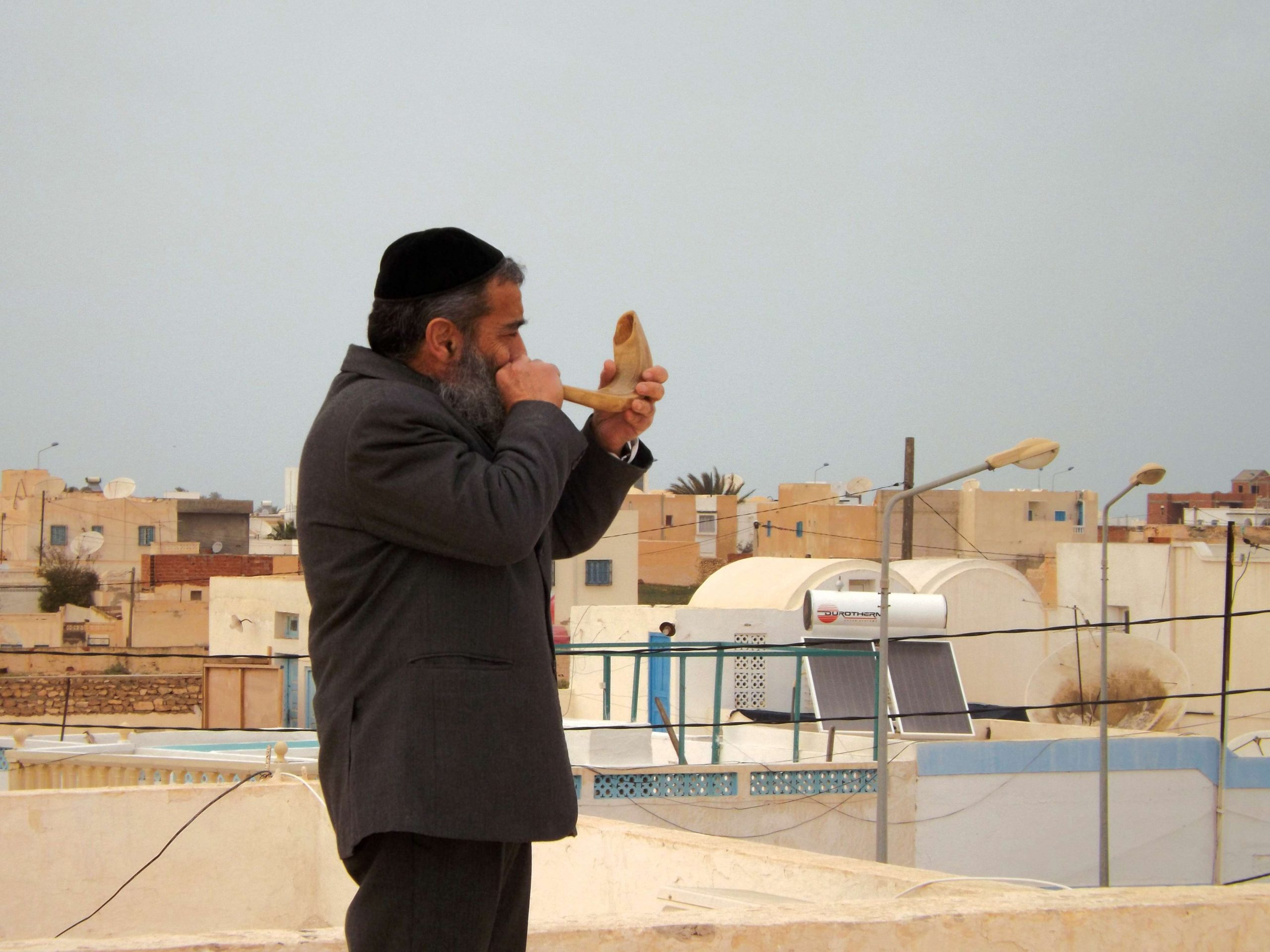 An ancient custom continues on the rooftops of Djerba. Rabbi Chaim Biton with his shofar