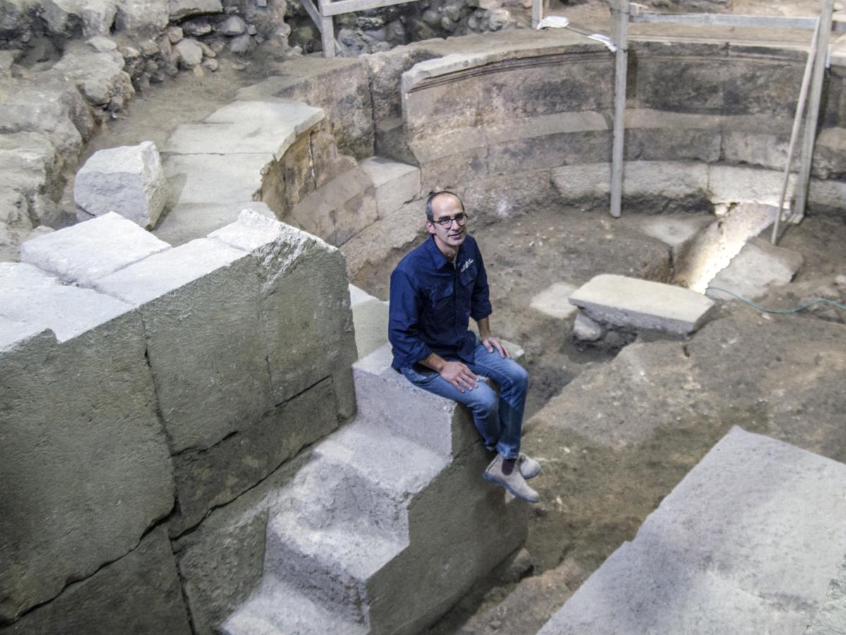הארכיאולוג ג'ו עוזיאל מיושב על מדרגות המבנה דמוי התיאטרון בחפירת קשת וילסון