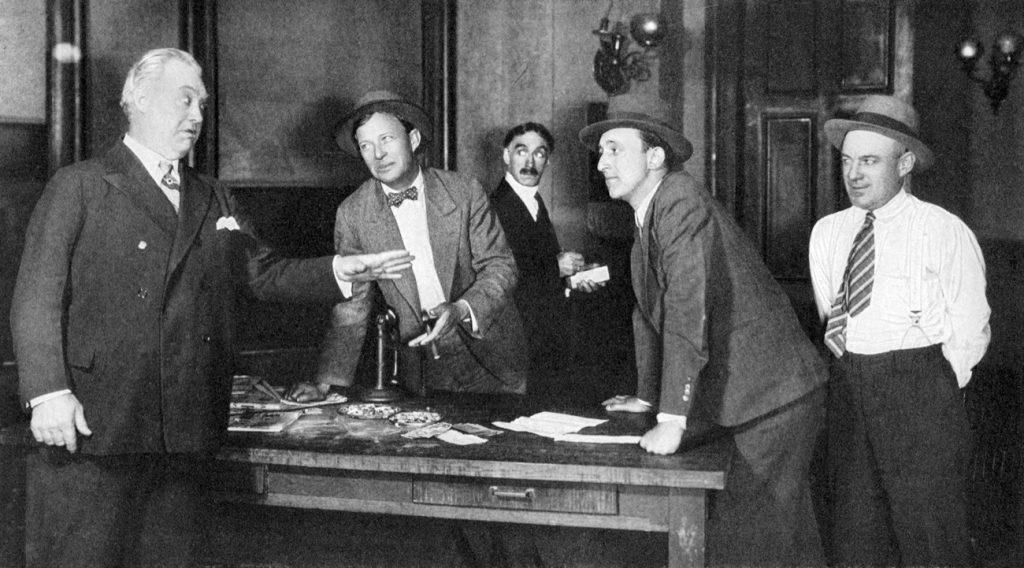 סצנה מתוך 'העמוד הקדמי', קומדיה פרי עטם של הכט ומקארתור שהועלתה על הבמה בברודווי ב־1928. תמונה מתוך מאמר ביקורת על המחזה שהופיע ב'Theatre Magazine'
