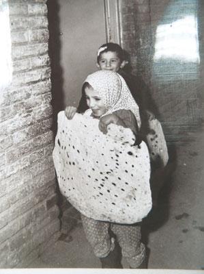 מצות בקוטר מטר. ילדה יהודייה באיראן מחזיקה מצה טיפוסית של הקהילה. שנות השבעים של המאה העשרים