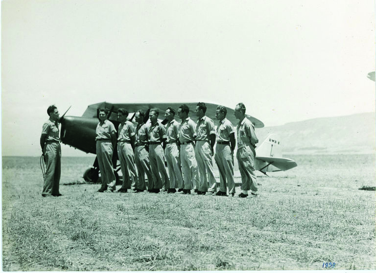 Emanuel Zurr (left) and graduates of Mandate Palestine's first pilots' course pose in front of an RWD-8 plane owned by Aviron at the Afikim airfield, 1939
