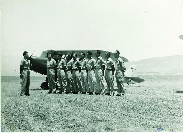 עמנואל צור (משמאל) בטכס סיום קורס הטיס הראשון בארץ ישראל. מאחור מטוס RWD-8, חברת אוירון, מנחת אפיקים, 1938