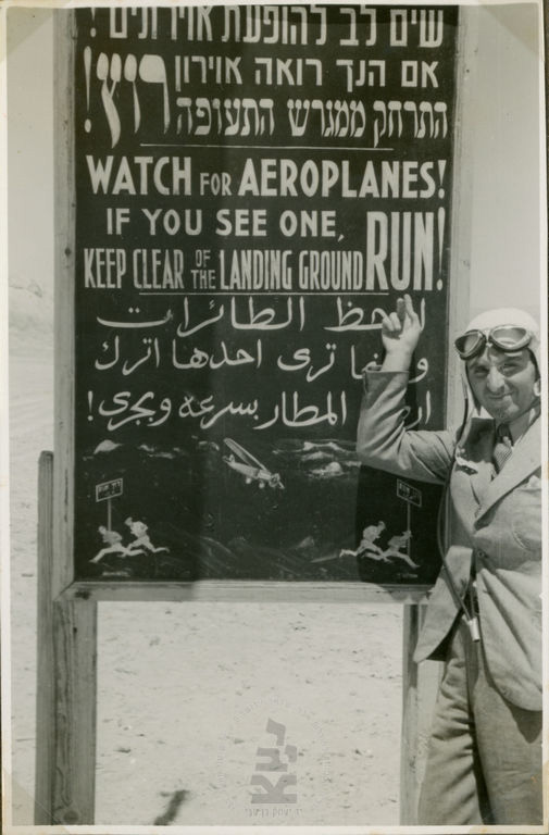 Zurr pointing to a sign in Hebrew, English, and Arabic (with a pictogram for the illiterate!) warning against moving aircraft at the Ashlag company airfield, Sodom, 1938–9