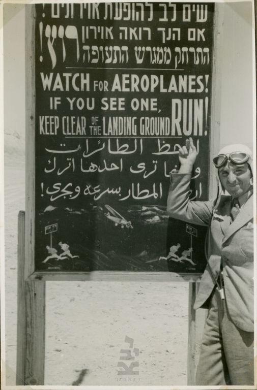 עמנואל צור מצביע על שלט אזהרה מתנועת מטוסים, מנחת חברת האשלג, סדום, 1938-9