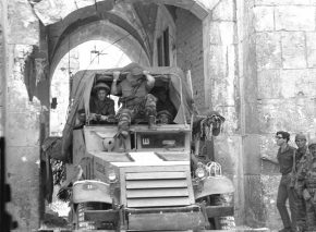 Command car passing through Lions' Gate behind the advance attack force