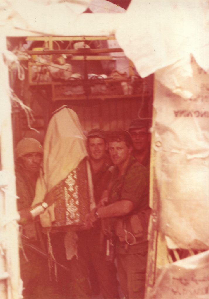 A Torah scroll is dedicated in the heart of enemy territory. Paratroopers escort the scroll from the historic synagogue to their own makeshift one in the battalion compound – a camouflage net stretched between two bulldozers