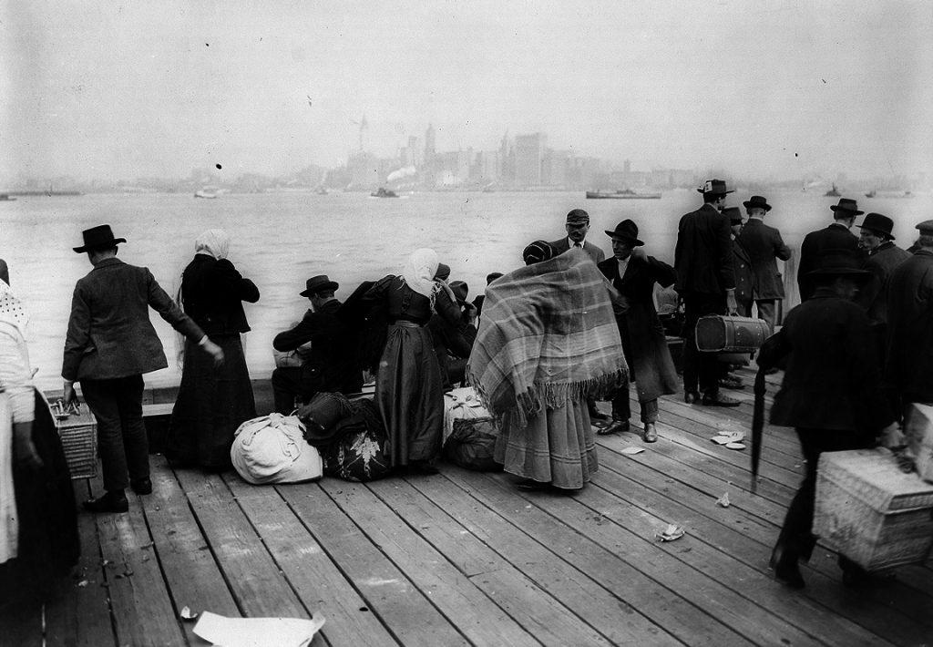 התחנה האחרונה בדרך לארץ המובטחת. מהגרים ממתינים על הרציף באליס איילנד לסירה שתיקח אותם לניו יורק, 1912