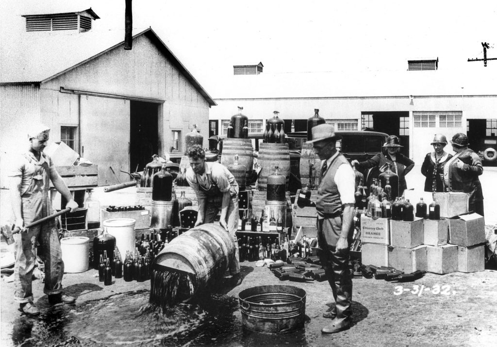 Orange County sheriff's deputies pouring away illegal alcohol, Santa Ana, California, March 1932