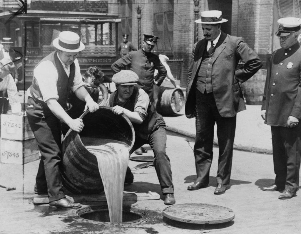 שוטר משגיח בזמן שאלכוהול מוחרם נשפך ברחובות העיר ניו יורק, 1921