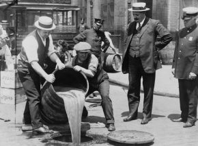 A policeman supervises the disposal of confiscated liquor on the streets of New York, 1921