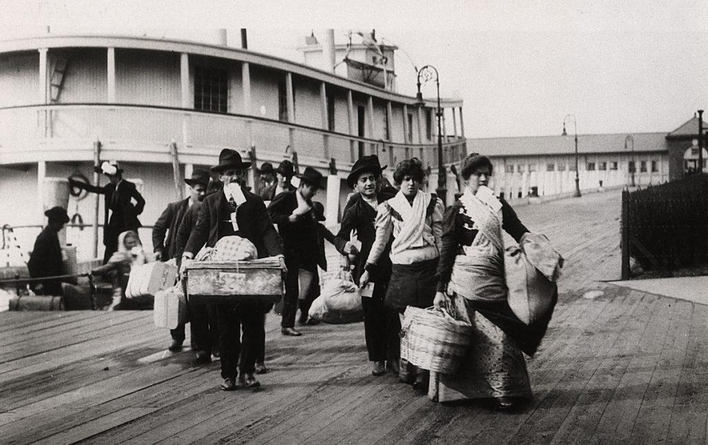 אל המזח. מהגרים יורדים מהספינה באליס איילנד, נמל ניו יורק