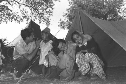 Two soldiers entertain immigrant children at a transit camp in Kisalon, December 1950