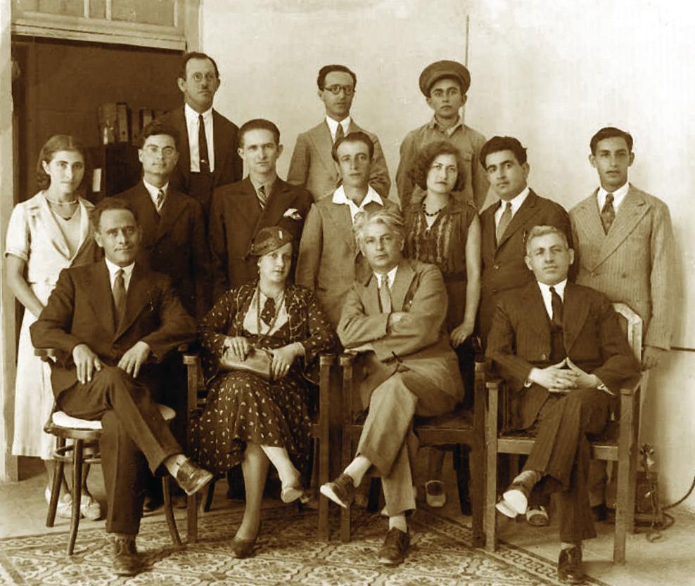 """מערכת העיתון 'דֹאר היום'. במרכז יושבים איתמר בן-אב""""י ורעייתו לאה לבית אבושדיד שסיפור אהבתם תואר בסיפורים ובשירים. שנות העשרים של המאה העשרים"""