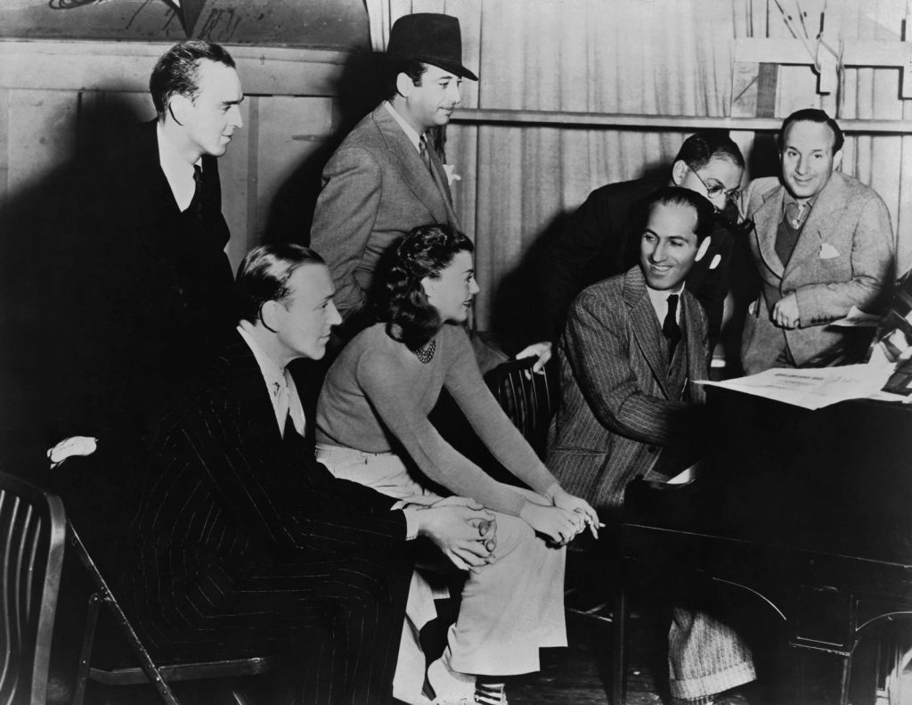 Gershwin at the piano with Fred Astaire, Ginger Rogers and musical directors of Shall We Dance, 1937, just months before his death that July