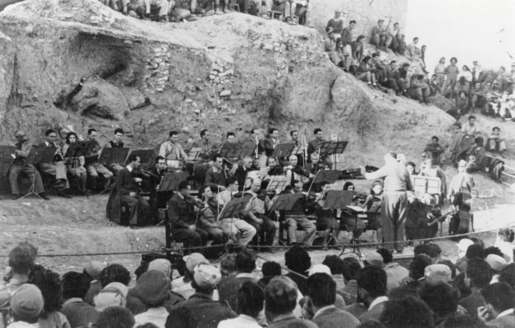 קונצרט במדבר. העולים מגרמניה היו פחות מרבע מכלל העולים בעלייה החמישית, אך הם תרמו רבות בתחומים מקצועיים ותרבותיים והביאו לתנופה צרכנית ותעשייתית. התזמורת הפילהרמונית הישראלית שהוקמה על ידי עולים מגרמניה בהופעה בבאר שבע, 1948