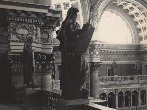 Side by side, statues of Moses and Newton look down from the gallery of the American Library of Congress