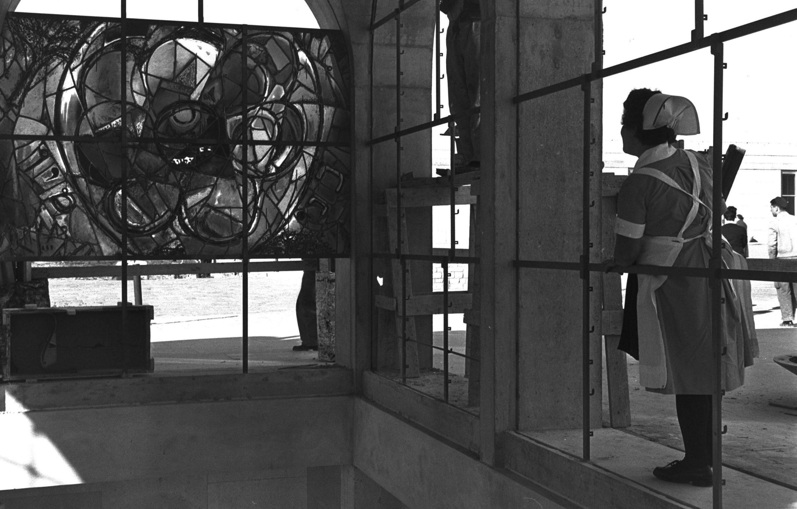 """אחות מתבוננת על הוויטרז'ים המפורסמים בבית הכנסת שבבית החולים הדסה עין כרם סמוך להתקנתם בתשכ""""ב צילום: משה פרידן, לע""""מ"""