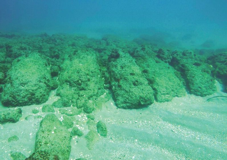 Carved sandstone ashlars, all laid as headers to blunt the impact of the waves, now lie at a depth of some five meters. They once formed part of the jetty shoreward of the southern breakwater. Below, part of the Herodian wharf in the northern part of the middle harbor. The similarity between the two is clear, though today only one is above water