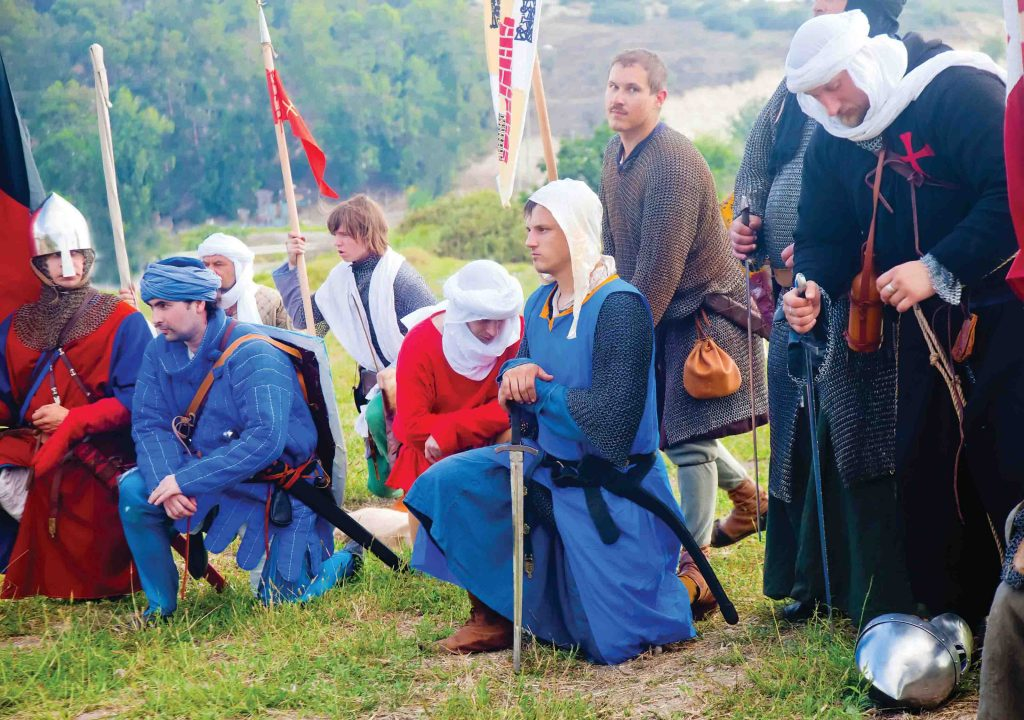 "Reenacting historic battles is a fast-growing hobby in Israel. Every summer, actors divided into Crusaders knights and Saracen soldiers recreate the Battle of Hattin. ""Crusaders"" kneel in prayer before going out to war, Zippori, 2014"