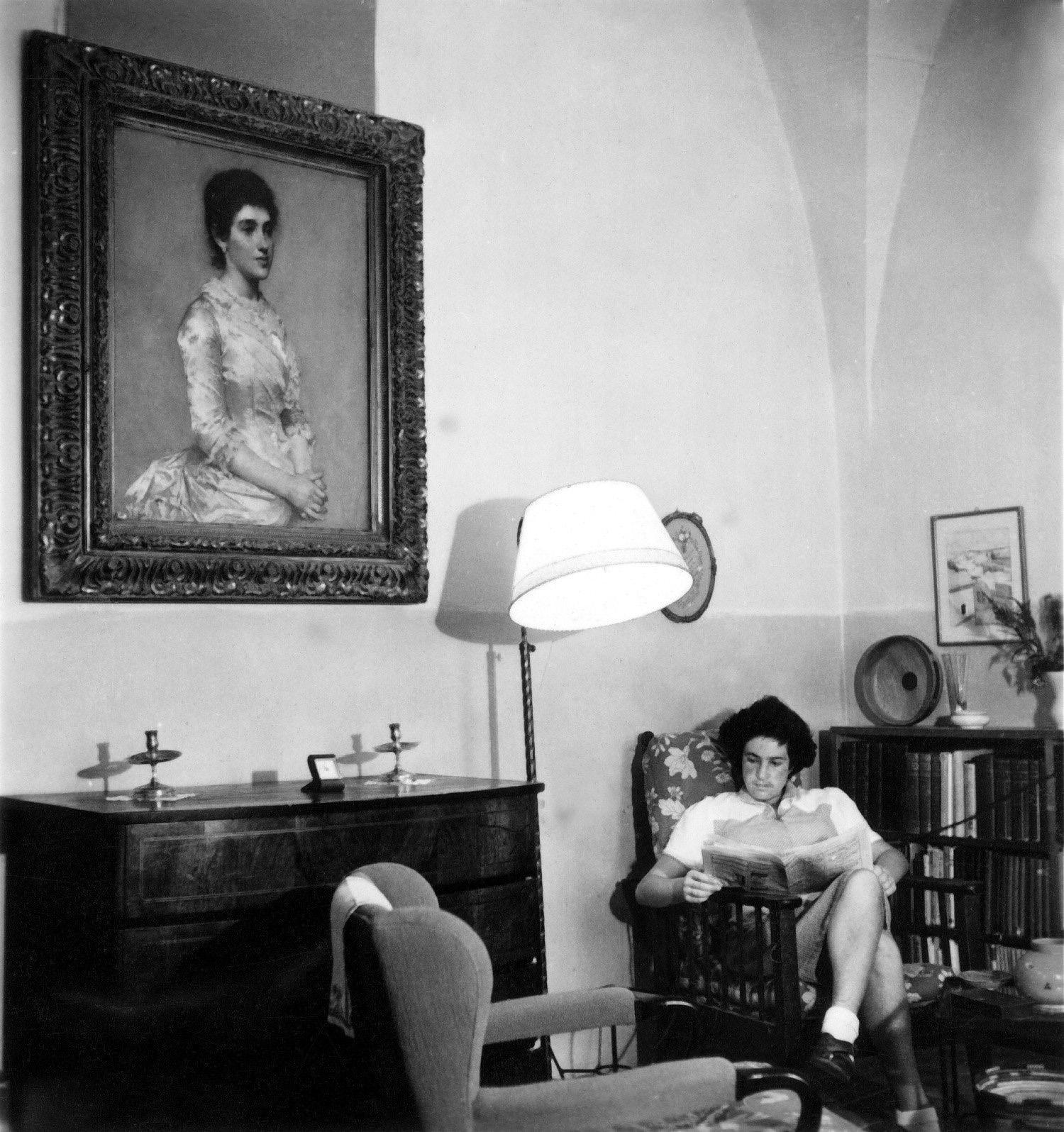 תלמה ילין קוראת בטרקלין ביתה בירושלים. מעליה מתנוסס דיוקן מצויר שלה