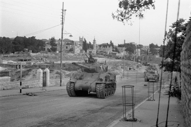 Tanks lead a convoy of trucks carrying troops toward East Jerusalem