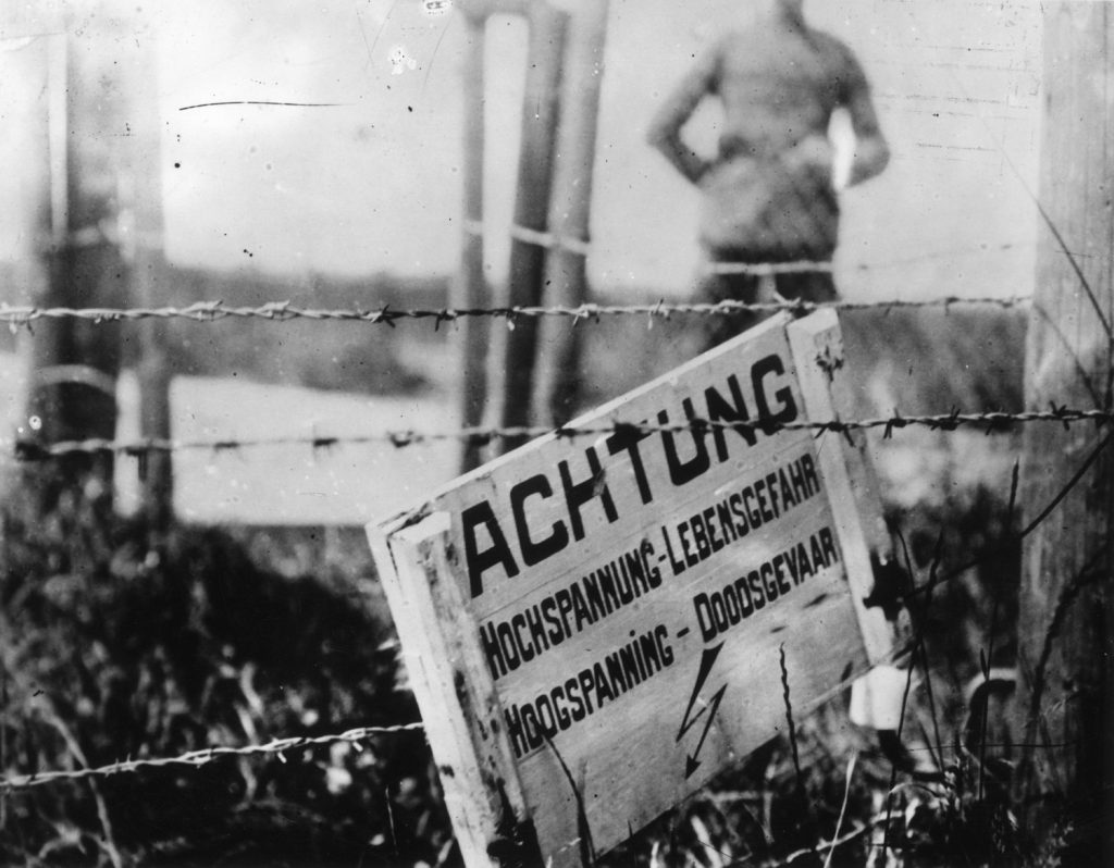 Barbed wire fencing was a devilishly simple invention put to lethal use at the front. Electrical charges made these fences doubly effective. Sign in German on the Belgian-Dutch border in World War I, warning of an electrified fence