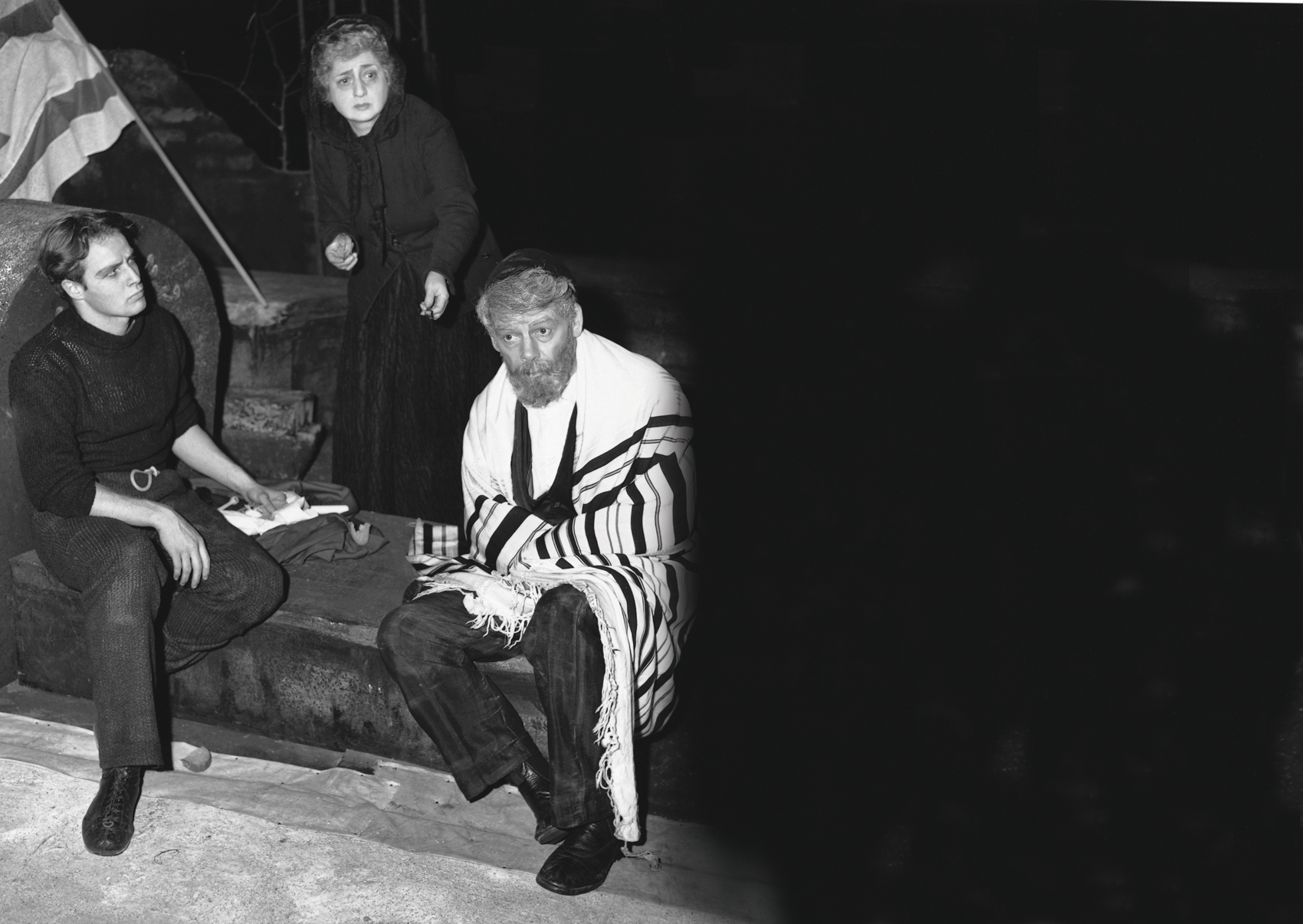 Everyone involved in A Flag Is Born had rallied to Ben Hecht's call, and many volunteered their services. Celia Adler, first lady of the Yiddish stage, played the heroine alongside Paul Muni and Marlon Brando. Muni (left), Adler, and Brando rehearse before opening night