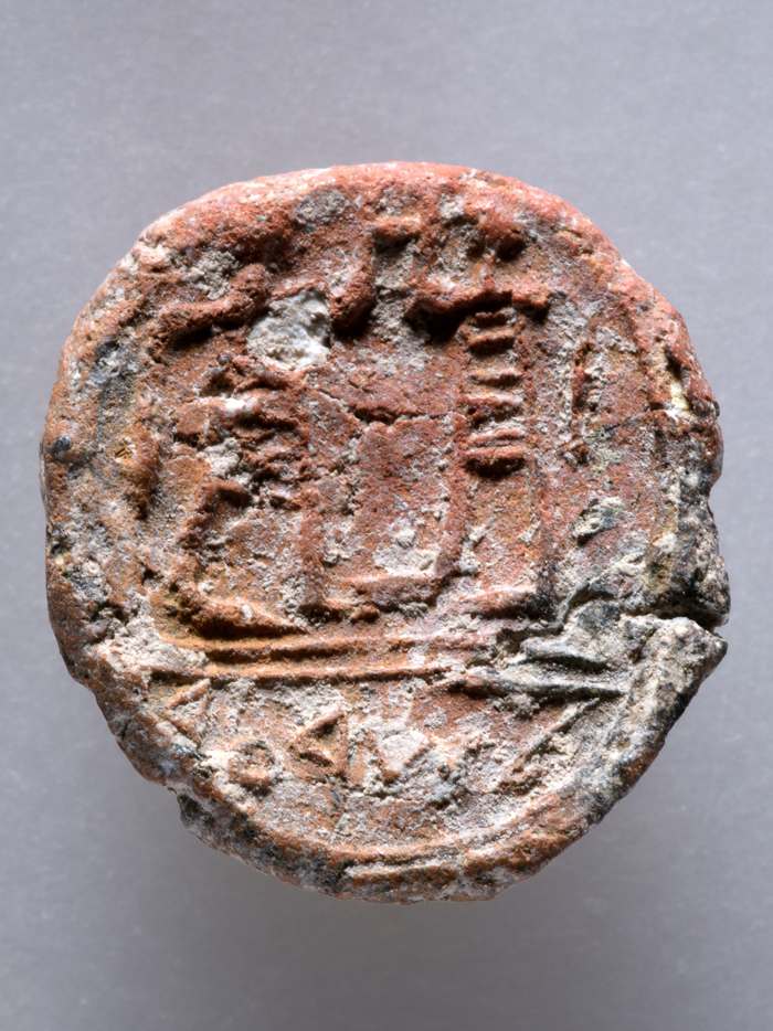 "The tiny clay disc shows the imprint of a seal carved with two male figures above the inscription ""to the City governor"""