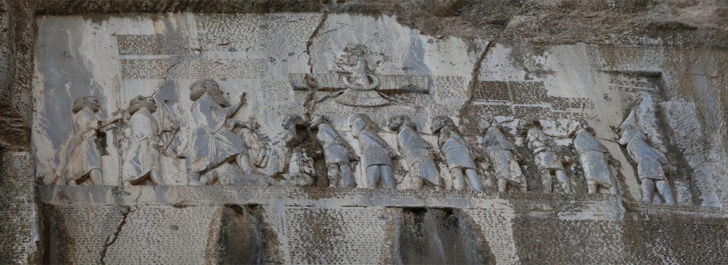 כתובת ביסותון, המתארת את ניצחונותיו של דריווש הראשון, פותחת בהכרזה על כך שמלכותו של דריווש ניתנה לו בחסדו של אהורה מאזדה. דריווש במרכז ומולו אויבים שבויים