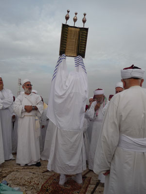 A Samaritan Torah scroll is raised on high during the thrice-yearly pilgrimage around the six holy sites of Mount Gerizim. Although all members of the community attend, men and women walk separately