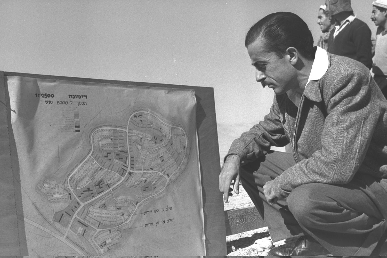 למרות קשיי ההתחלה נרתמו רבים מהעולים לפיתוח האזורים שבהם התיישבו. יגאל אל על, מזכיר דימונה, מביט בתכנית היישוב, 1955