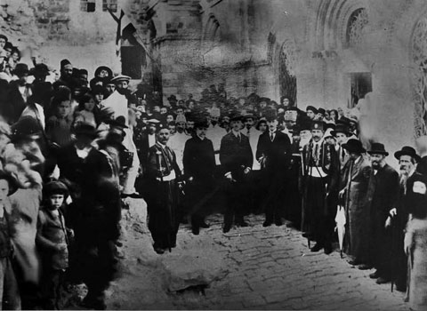 Franz Joseph and his entourage in the courtyard of the Ruzhyn synagogue in Jerusalem. Nisan Beck, marked by his long, white beard, appears at far left. This photo affords a rare glimpse of Beck, who generally refused to be photographed, citing the biblical injunction against graven images
