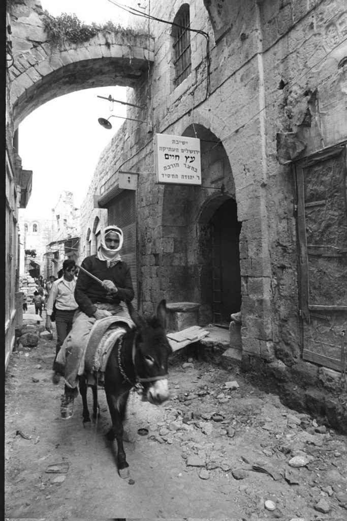 Neighborly relations developed between some coop members and Arab residents of the Old City, while others were suspicious and hostile. Arabs passing the ruined entrance to the Hurva Synagogue, in which the kabbalistic Etz Haim Yeshiva temporarily set up shop. March 1972