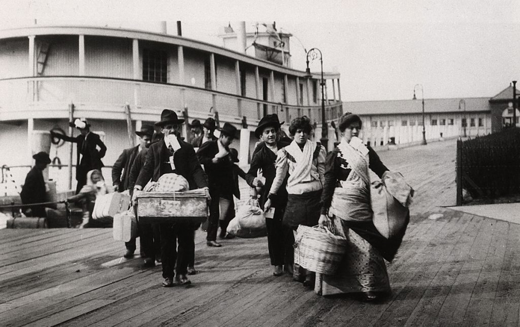 At the docks. Immigrants disembark at Ellis Island, New York Harbor