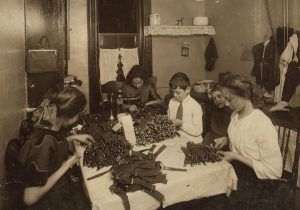 "A Jewish family working on garters in its tenement kitchen in New York, 1912. Like other immigrants, the Jews lived in terribly crowded conditions. While the first generation focused on economic survival, the second and third left the ""ghetto"" for the more spacious suburbs"