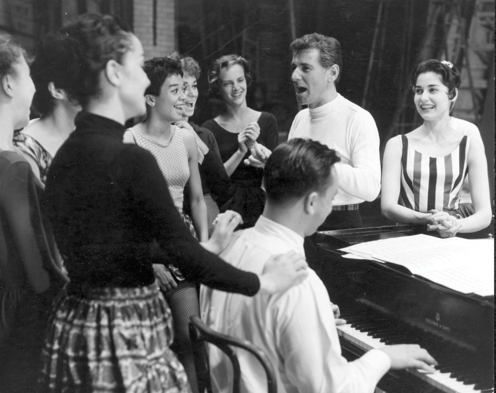 Leonard Bernstein at a rehearsal for West Side Story in 1957. Carol Lawrence (who played Maria) is leaning on the piano to his left, and lyricist Stephen Sondheim is at the piano