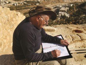 אהוד נצר יושב באתר החפירה בהרודיון ומשרטט את הצעתו לשחזור קברו של הורדוס בתערוכה. התמונה צולמה שעות ספורות לפני הנפילה שהביאה למותו