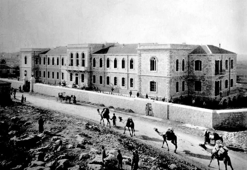 """בית החולים שערי צדק נוסד על ידי ד""""ר משה וולאך בשליחות ועד הפקידים של אמסטרדם, ונקרא אז 'בית החולים האמסטרדמי'. דה האן, שעלה מהולנד, היה מקורב לד""""ר וולאך. בית החולים שערי צדק על דרך יפו, 1905 לערך"""