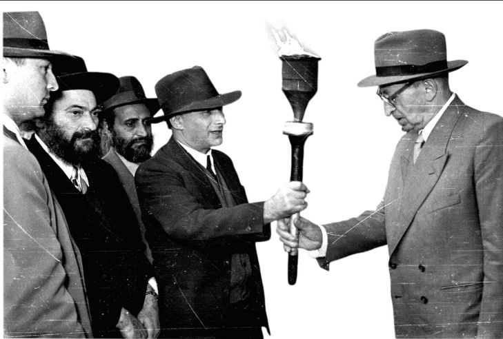 On Hanukka, a Ministry of Religious Affairs delegation led by S. Z. Kahane hands President Yitzhak Ben-Zvi a torch lit at the Beacon in Modi'in