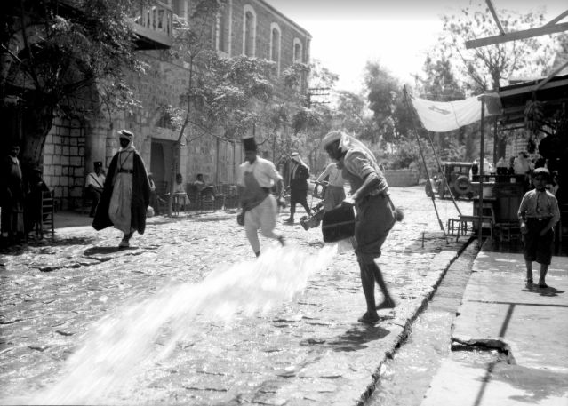 Beth She'an's distinctive black basalt buildings and pavement derive from the volcanic rock of the Galilee. Washing the streets, 1920
