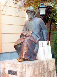 """עיצוב דמותו של רמב""""ם בפסלו של אמדאו רויז אולמוס שהוצג בקורדובה ב-1964 הושפע מזה של פטנאם אבל משמר את הכובע מהציור המוכר"""